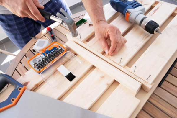 hands-driving-nail-with-hammer-into-wooden-shelf_74855-5668